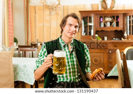 Young man in traditional Bavarian Tracht in restaurant or pub with beer and steins and pretzel - stock photo