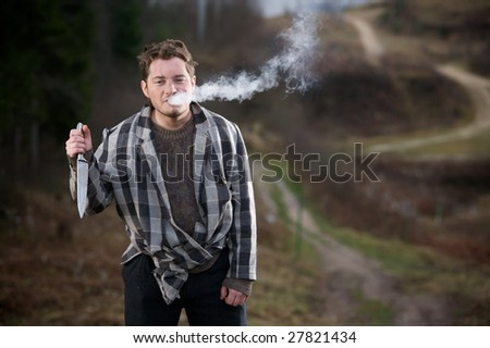 Young man in unkempt layered clothing, blowing cigarette smoke from his mouth, holding a knife at chest level in his right hand.  Taken in a rural setting. - stock photo