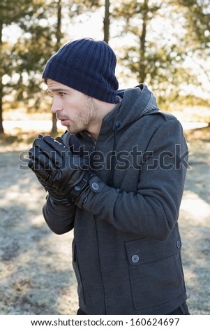 Young man in warm clothing shivering while having a walk in forest on a winter day - stock photo