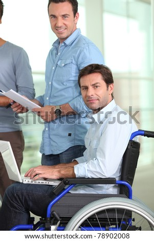 Young man in wheelchair at work - stock photo