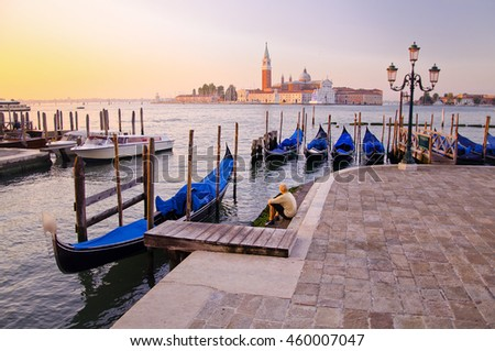 Young man in white clothes sitting in front of Grand Canal in Venice with gondolas against San Giorgio Maggiore church in Italy. Scenery from summer vacation with beautiful colorful morning light.  - stock photo