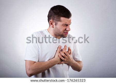 Young man in white t-shirt with strong heart attack - stock photo