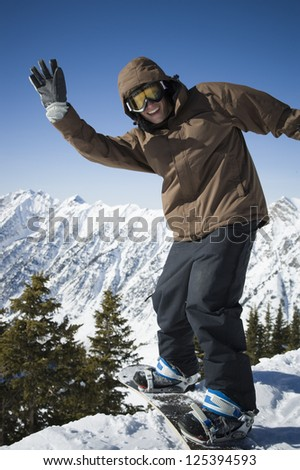 Young man in winter coat snowboarding - stock photo