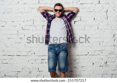 Young man in with sunglasses smiles happily with his hands behind his head. - stock photo