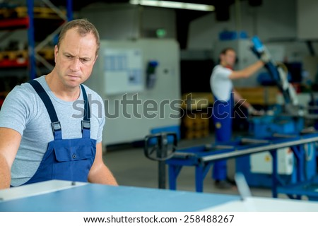 young man in workwear is  busy in factory - stock photo