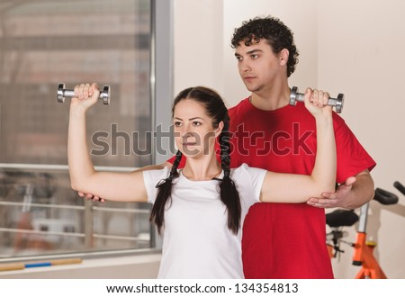 young man instructs woman with dumbbells in fitness club - stock photo