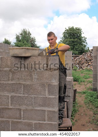 Young man is building house walls from concrete blocks. - stock photo