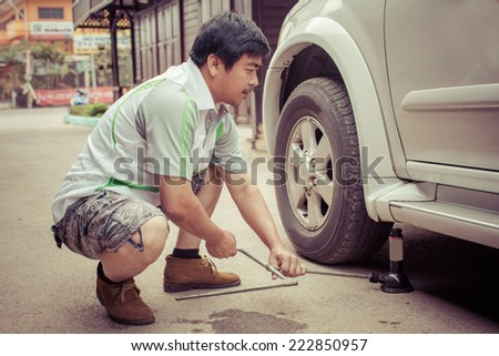 Young man is changing tire of he car with wheel wrench. process color - stock photo
