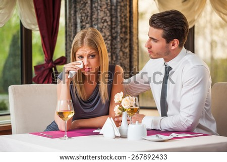 Young man is consoling his girlfriend at the restaurant - stock photo