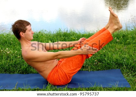 Young man is doing his yoga practice - stock photo