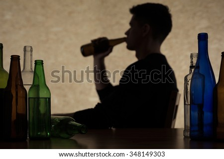 Young man is drinking too much alcohol - stock photo
