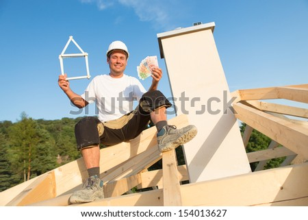 Young man is happy with new house and money in his hands - stock photo