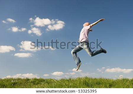 Young man is jumping over a green. Use it for lifesytle concepts - stock photo