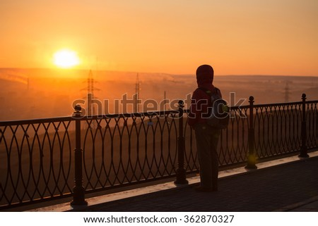 Young man is looking at the sunset. - stock photo
