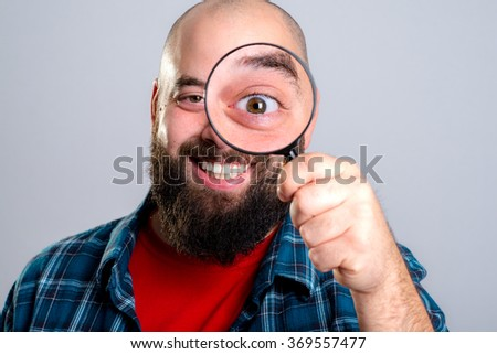 young man is looking through magnifying glass - stock photo