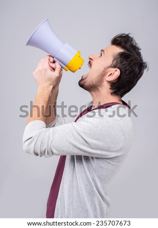 Young man is making announcement over a megaphone on the gray background. - stock photo