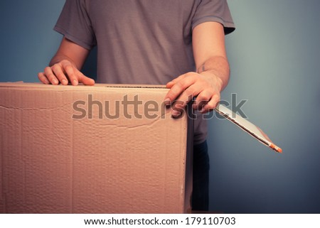 Young man is moving house and is holding a large cardboard box - stock photo