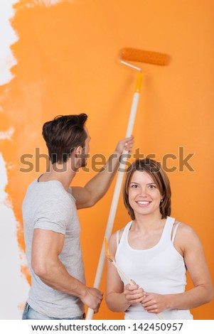 Young man is painting a wall and girlfriend smiles - stock photo