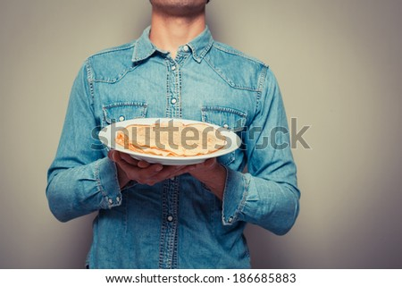 Young man is presenting a plate with a stack of pancakes - stock photo