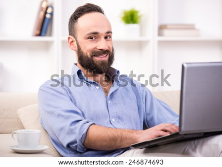 Young man is relaxing at home using laptop and drinking coffee. - stock photo