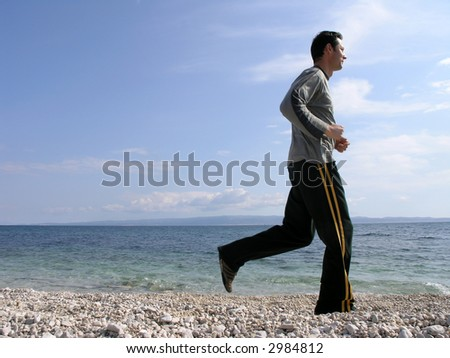Young man is running along the shore in a sunny day . - stock photo