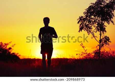 Young man is running at the sunset - stock photo
