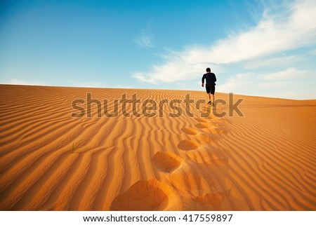 Young man is running to the top of dune in desert - stock photo
