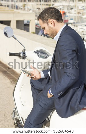 Young man is sitting on scooter and looking his phone. - stock photo