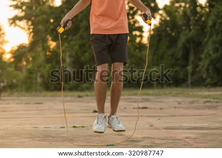 young man is skipping with a jump rope in the park on a summer d - stock photo