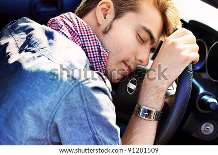 Young man is sleeping in a car. - stock photo