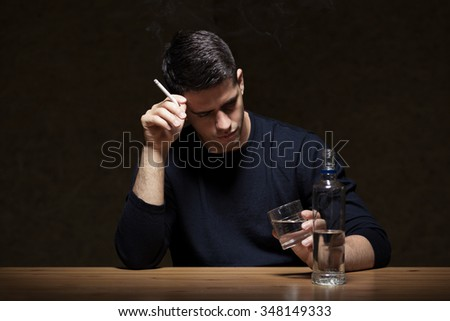 Young man is smoking and drinking some vodka - stock photo