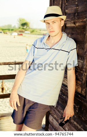 Young man is standing on a bech tower. - stock photo