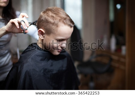 Young man is using Hairdresser making haircut to young man at beauty parlour. Fashion male model behind the scene - stock photo