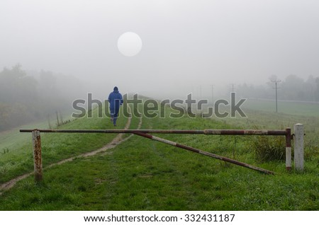 Young man jogging in nature on cold misty autumn day. - stock photo
