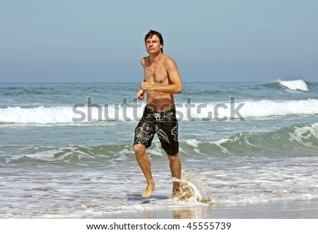 Young man jogging on the beach - stock photo