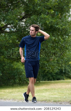 Young man jogging outdoors in sports clothing - stock photo