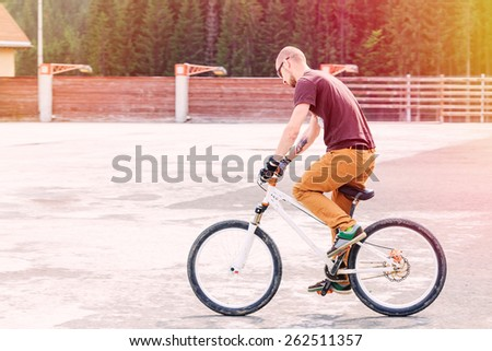 Young man jump on bicycle through the white line. - stock photo