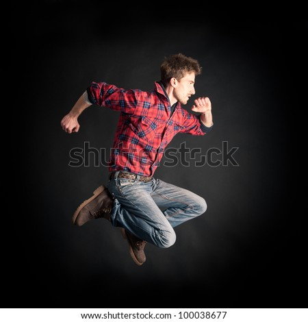 Young man jumping against black background. - stock photo