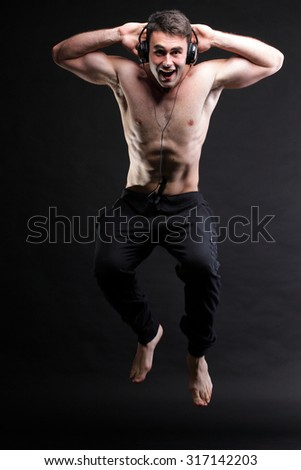 Young man jumping and listening music isolated over black background - stock photo