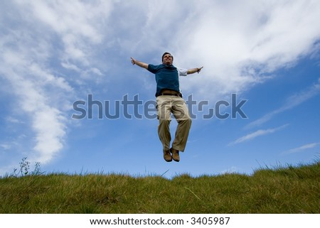 young man jumping in meadow - stock photo