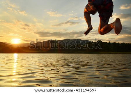 Young man jumping into the lake during calm summer sunset.  - stock photo