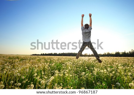 Young man jumping on a green meadow over blue clear sky background - stock photo