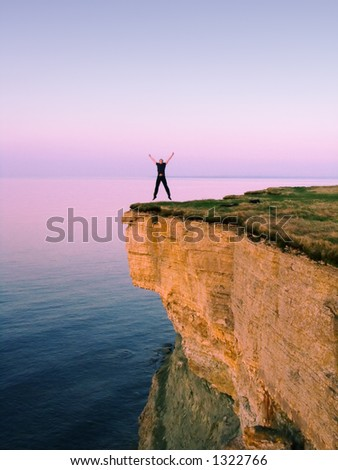 young man jumping on the cliff with spreaded hands - stock photo
