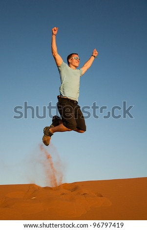 Young man jumping on the sand - stock photo