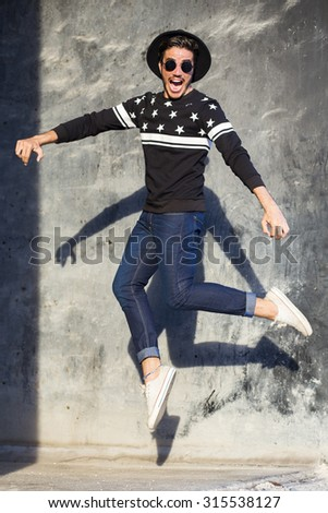 Young man jumping with a trendy outfit against a urban background - stock photo