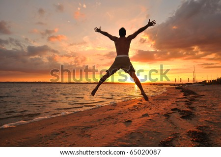 Young man jumping with spread arms celebrating and enjoying the moment at the seaside at sunset - stock photo