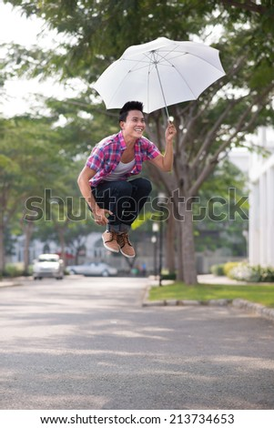 Young man jumping with umbrella outdoors - stock photo