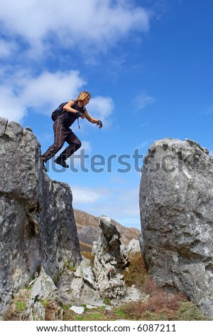 Young man jumps from rock with smile - low angle, against sky. Shot in Hottentots-Holland Mountains nature reserve, near Grabouw, Western Cape, South Africa. - stock photo