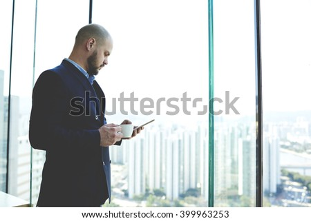 Young man jurist is reading the new bill in internet via mobile phone during coffee break in work day. Male skilled CEO is watching video on cell telephone, while is resting after meeting with clients - stock photo
