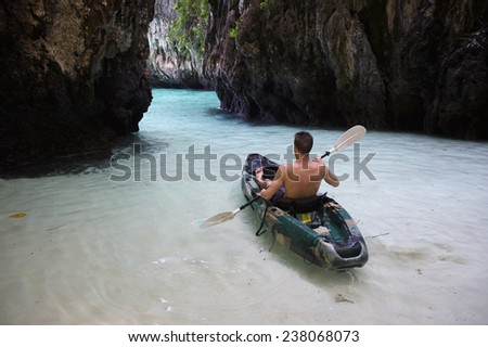 Young man kayaking through shallow tropical waters toward narrow rock cove - stock photo